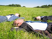 businessmen lying on grass