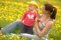 Pregnant mother and baby, girl, in a spring meadow