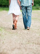 Couple walking in countryside field