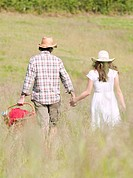 couple in hats walking through meadow