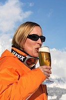 Female skier enjoying a glass of beer