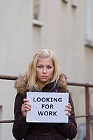 Young woman holding a sign Looking for work, symbolic picture for the economic crisis