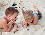 Two boys 5 and 6 years old watching a hermit crab on the beach