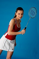 portrait of a young darkhaired woman in sport outfit, playing badminton