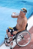 Young, handicapped man in a wheelchair at the edge of a swimming pool, drinking water, view from the side