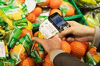 Scanning the price of packaged fruit into a cell phone in order to pay via cell phone in the real, _ Future Store, part of the Metro Group, in Toenisv...