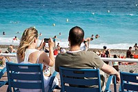 Couple sitting on blue chairs taking a photo of the beach, Promenade des Anglais, Nice, Provence, France