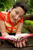 Latino woman reading book.
