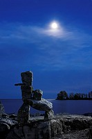 Stone human figure under moonlight on a shore of lake Ontario in Toronto Inukshuk Inuit culture Spiritual symbol Atmospheric dramatic nighttime scener...