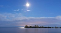 Beautiful atmospheric panoramic view on lake Ontario after sunset with moonlight from a glowing moon in the sky reflecting in the water Toronto, Ontar...