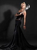 Beautiful woman in long elegant black skirt holding a venetian mask standing in a spotlight