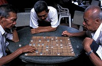 Three senior men playing traditional board game