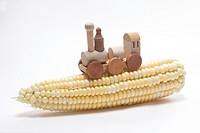 A wooden train piece atop an ear of raw corn  Biofuel concept