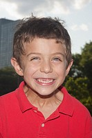 Headshot of a a seven year old boy smiling  His two front teeth are missing