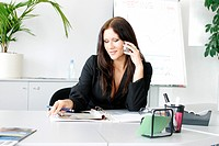 woman in office using mobile phone.