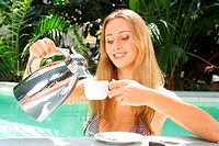 blond woman standing at the edge of a swimming pools pouring beverage into a cup.