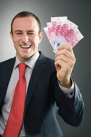 Smiling businessman with bank notes