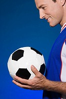 Smiling footballer holding a football
