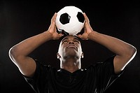 Man balancing a football on head