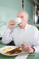 Senior man eating breakfast in a diner
