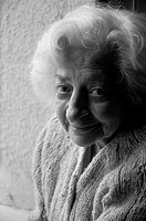Portrait of old woman smiling and looking at the camera. Black and White.