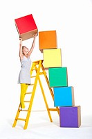 Woman stacking coloured boxes