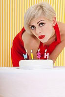 Woman blowing candles that say wish
