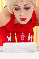 Woman blowing candles that spell wish