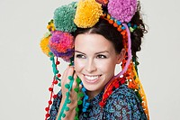 Young woman wearing pom pom headdress