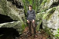 Young man standing by rocks (thumbnail)