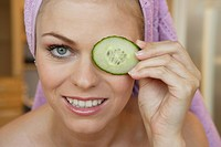 young woman preparing a face mask, holding cucumber slice in front of her eye