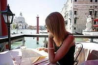 Woman looking at menu in alfresco cafe