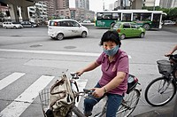 a woman with a mask on the streets of Shanghai, China