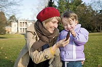 Mother and her 2-year-old daughter looking at a pine cone during a walk in the Rieter Park, in front of the Villa of the Rietberg Musuem in Zurich, Sw...