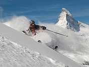 Helmeted free_rider skiing off piste with Matterhorn in the background