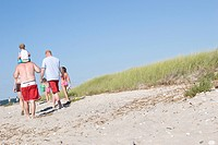 Family walking by grassy sand dunes on beach
