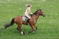 Horsewoman on horseback galloping through a green meadow