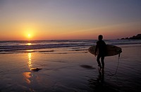 Silhouetted surfer on sandy beach at sunset