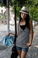 Girl poses before the camera on a street in Shanghai, China