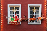 Christmas decoration, Santa on sleigh drawn by reindeer on a red house with white crown glass windows