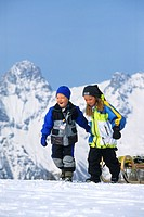 two children in the mountains with a sled, Austria, Alps