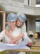 Couple looking at blueprints at construction site