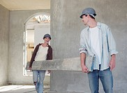 Couple carrying wood plank in house under construction