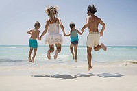 Family holding hands and jumping on beach