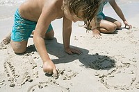 Boy and girl writing in sand on beach