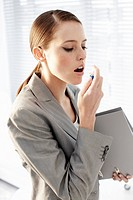 Businesswoman using breath spray