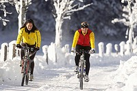 two women mountainbiking in a snowy mountain landscape, Austria, Alps