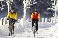 two women mountainbiking in a snowy mountain landscape, Austria, Alps