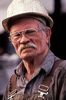 Smiling, mature construction worker with mustache in eyeglasses and hard_hat