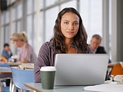 Confident college student using laptop in cafeteria